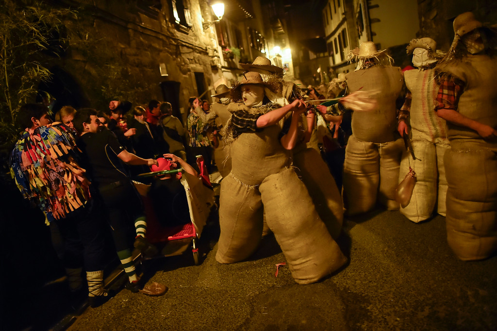 ". People dressed as the traditional carnival characters ""Zaku Zaharrak,\"" or old sack, in Basque language, as they take part in a carnival parade in the small Pyrenean village of Lesaka, northern Spain, Sunday, Feb. 26, 2017. After the sun set and covering their faces with white handkerchiefs, stuffed into sacks full of straw, and holding a stick with an inflated animal\'s bladder used to hit people, the Zaku Zaharrak characters parade for hours trough the village dancing and singing while a band plays music. (AP Photo/Alvaro Barrientos)"