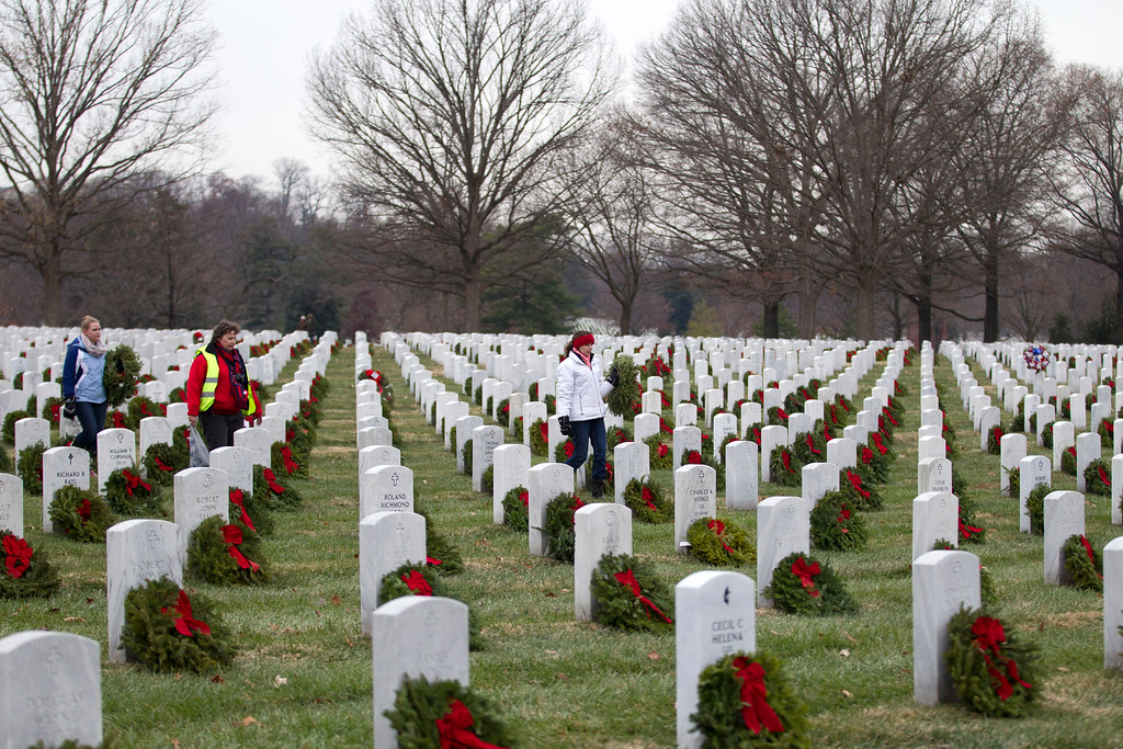 . Volunteers help to lay holiday wreaths at graves at Arlington National Cemetery in Arlington, Va., Saturday Dec. 14, 2013, during Wreaths Across America Day. Wreaths Across America was started in 1992 at Arlington National Cemetery by Maine businessman Morrill Worcester and has expanded to hundreds of veterans\' cemeteries and other locations in all 50 states and beyond. (AP Photo/Jose Luis Magana)