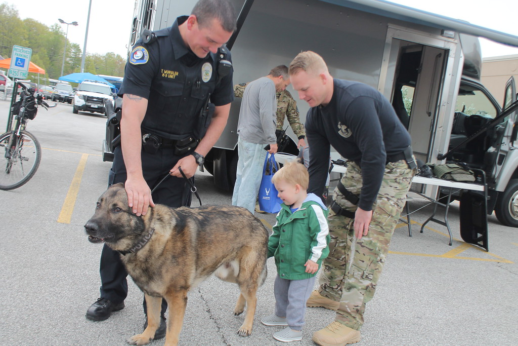 . Kristi Garabrandt � The News-Herald <br> Donnie Swindell of Mentor SWAT Department Mentor K-9 officer Terry Wurgler look on as Swindell\'s  two-year -old son Donnie pets Mentor\'s K-9 Titan , during the 36th Annual Heroes Day held at Great Lakes Mall, May 12, 2018.