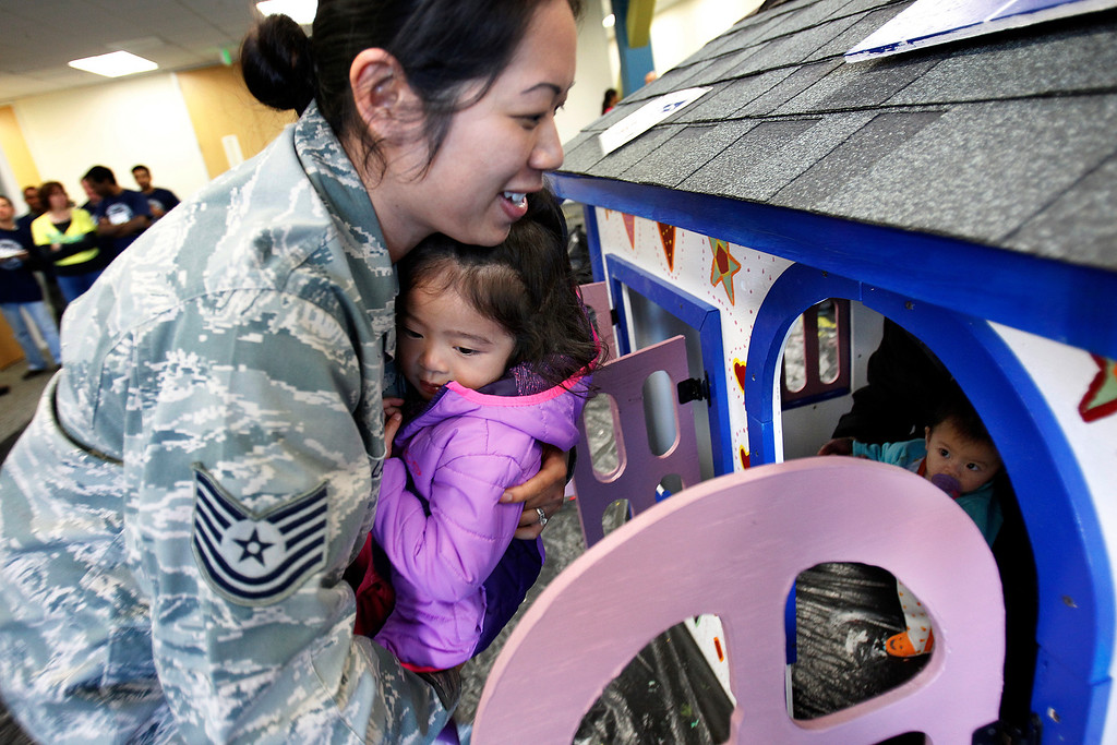 . From left, U.S. Air Force Tech Sergeant Jeannie Lam and her daughters Tessa Lam, 2, and Josie Lam, 1, check out their new playhouse that was built by NetScout Systems employees and Habitat for Humanity volunteers at the NetScout offices in San Jose, Calif. on Thursday, Feb. 21, 2013.   (LiPo Ching/Staff)