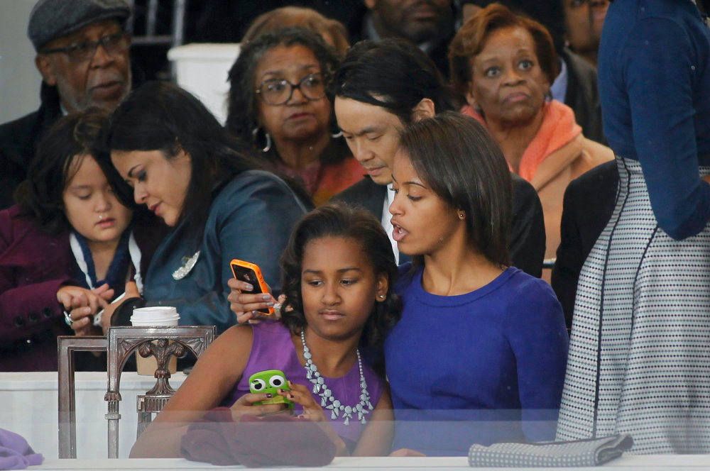 . Sasha (L) and Malia (R) Obama look at an iphone during the inaugural parade of their father, President Barack Obama, in Washington, January 21, 2013. REUTERS/Joe Skipper