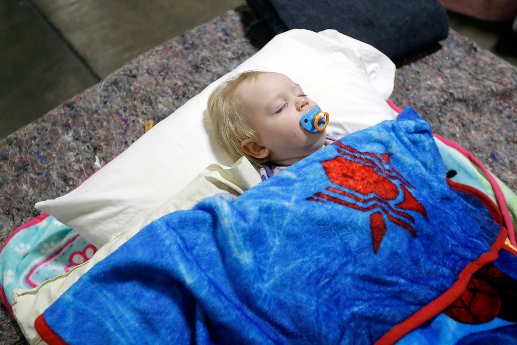 . Jace Lawson, 1, of Oroville, Calif., sleeps at a shelter for evacuees from city\'s surrounding the Oroville Dam Monday, Feb. 13, 2017, in Chico, Calif. The thousands of people who were ordered to leave their homes after a damaged California spillway threatened to unleash a 30-foot wall of water may not be able to return until significant erosion is repaired, authorities said Monday. (AP Photo/Marcio Jose Sanchez)