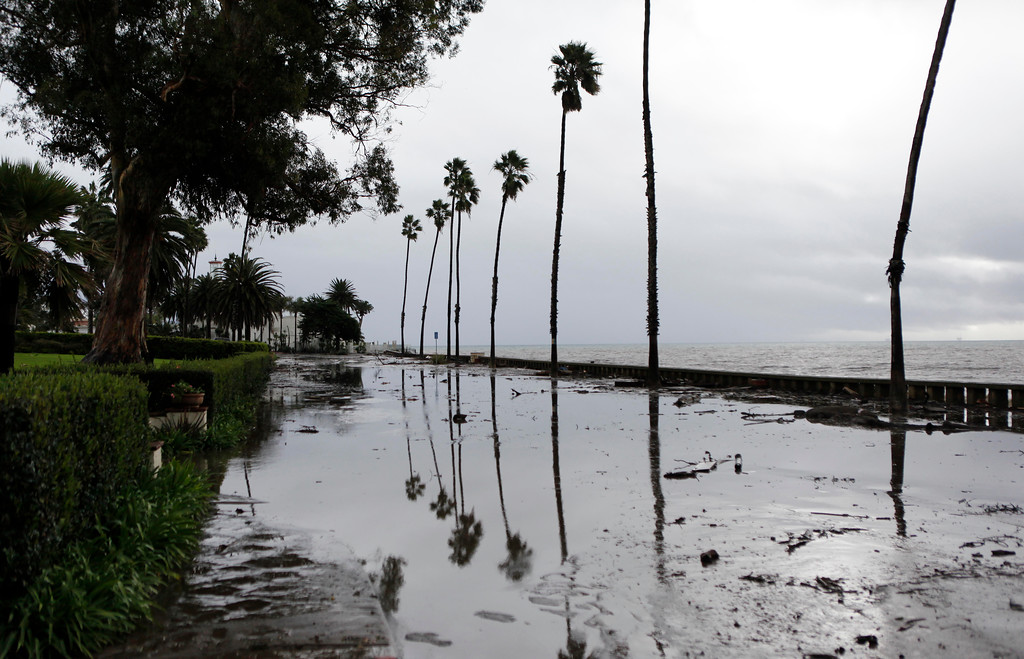 . The reflection of palm trees in mud and water along Channel Drive in front of The Fours Seasons Biltmore Resort in Montecito, Calif. on Tuesday, Jan. 9, 2018. Homes were swept from their foundations Tuesday as heavy rain sent mud and boulders sliding down hills stripped of vegetation by a gigantic wildfire that raged in Southern California last month. (AP Photo/Daniel Dreifuss)