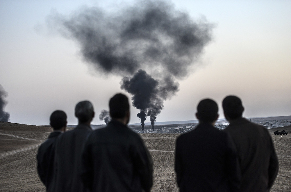 . People watch as smokes rises from the town of Kobane, also known as Ain al-Arab, on October 26, 2014, at the Turkish border near the southeastern village of Mursitpinar, Sanliurfa province.  AFP PHOTO / BULENT  KILIC/AFP/Getty Images