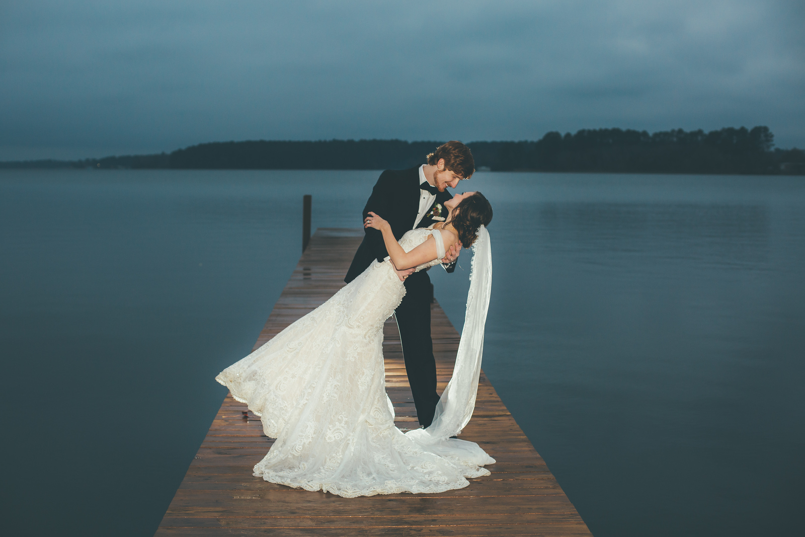 A groom dipping his bride on a dock in a lake at nightfall