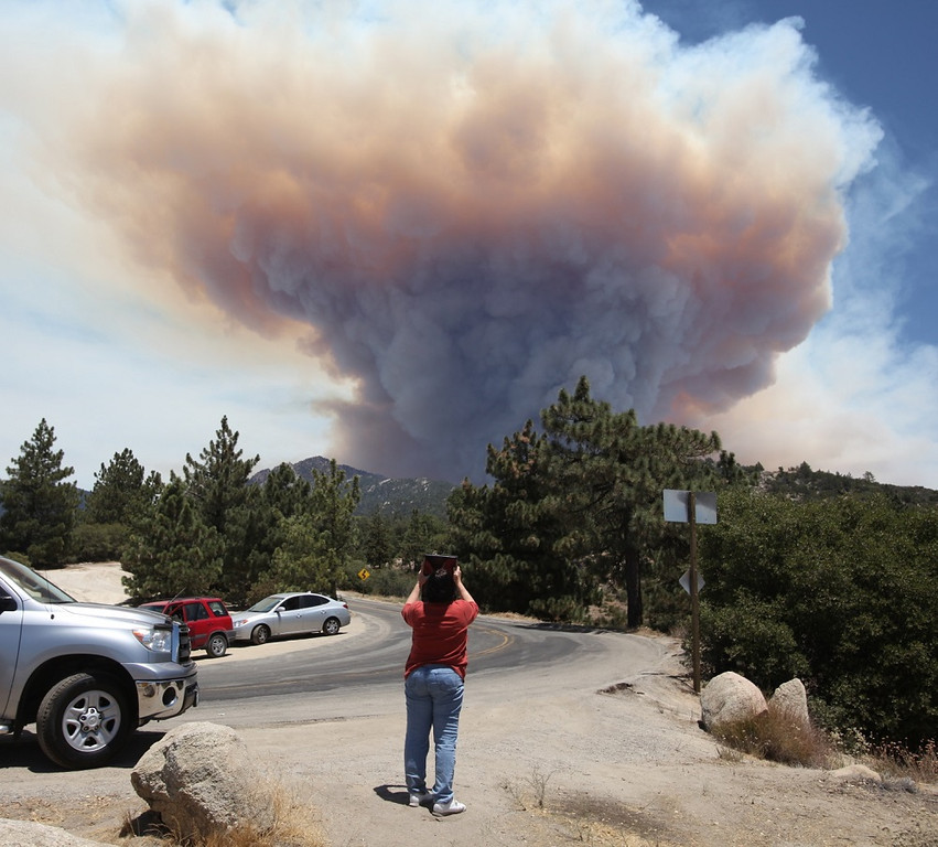 . Onlookers stop and take pictures of a large mushroom cloud of smoke coming from the Mountain Fire near Idyllwild, Calif., Wednesday, July 17, 2013. Authorities asked for additional evacuations as the wildfire in the mountains southwest of Palm Springs rages on. (AP Photo/The Desert Sun, Richard Lui)