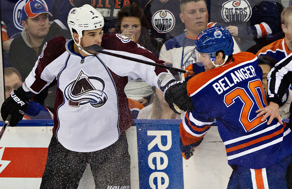 . Colorado Avalanche\'s Shane O\'Brien, left, gets a high stick from Edmonton Oilers\' Eric Belanger during the first period of their NHL hockey game, Monday, Jan. 28, 2013, in Edmonton, Alberta. (AP Photo/The Canadian Press, Jason Franson)