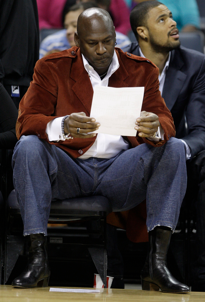 Description of . This March 1, 2010, file photo shows Michael Jordan looking over a stat sheet in the first half of the Charlotte Bobcats' 89-84 loss to the Dallas Mavericks in an NBA basketball game in Charlotte, N.C. The NBA has signed off on Michael Jordan's bid to buy the Charlotte Bobcats, and commissioner David Stern expects the league's board of governors to approve the purchase by the end of next week. (AP Photo/Chuck Burton, File)