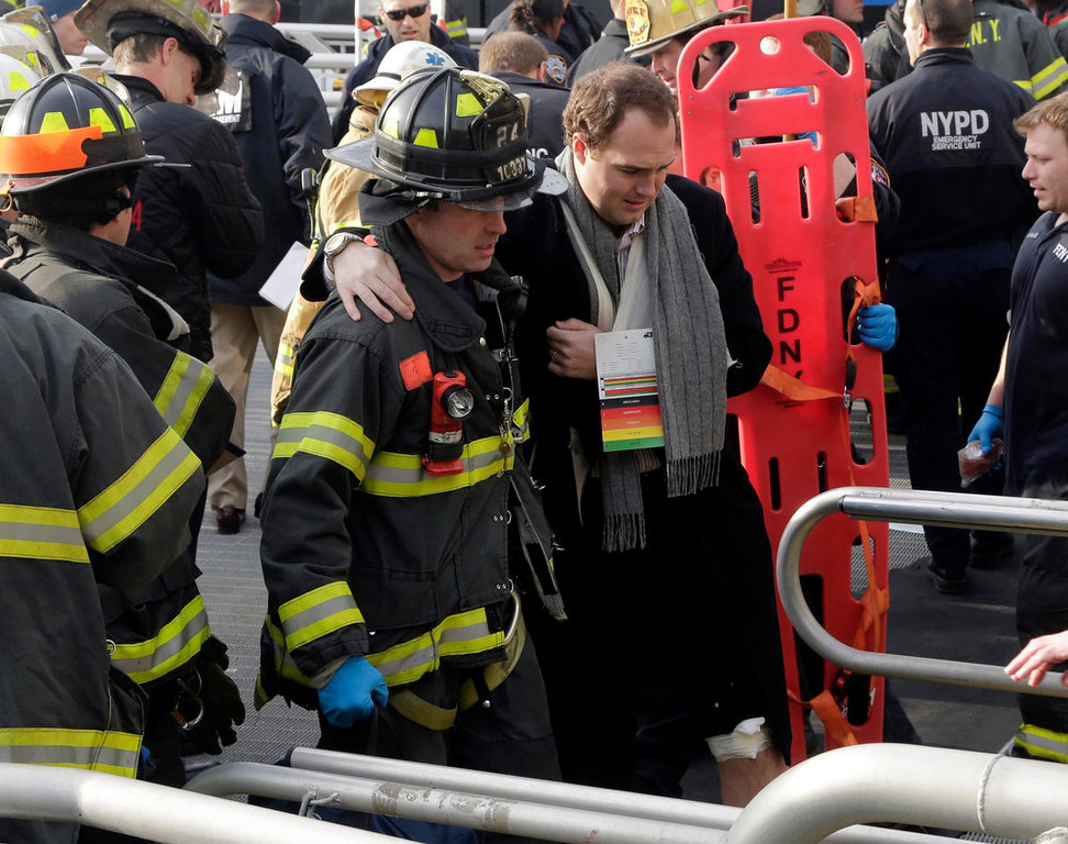 . An injured passenger from the Seastreak Wall Street ferry is taken to an ambulance, in New York,  Wednesday, Jan. 9, 2013. The  ferry from Atlantic Highlands, N.J., banged into the mooring as it arrived at South Street in lower Manhattan during morning rush hour, injuring as many as 50 people, at least one critically, officials said.(AP Photo/Richard Drew)