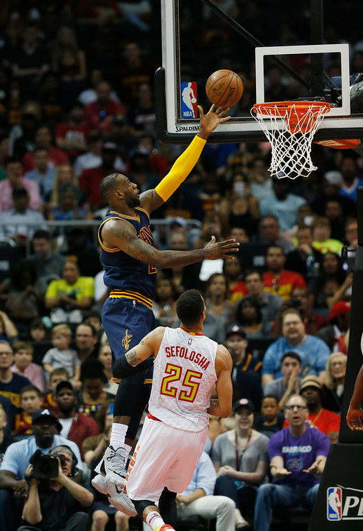 . Cleveland Cavaliers forward LeBron James (23) lays up the ball as Atlanta Hawks forward Thabo Sefolosha (25) looks on in of Game 4 of the second-round NBA basketball playoff series, Sunday, May 8, 2016, in Atlanta. (AP Photo/John Bazemore)