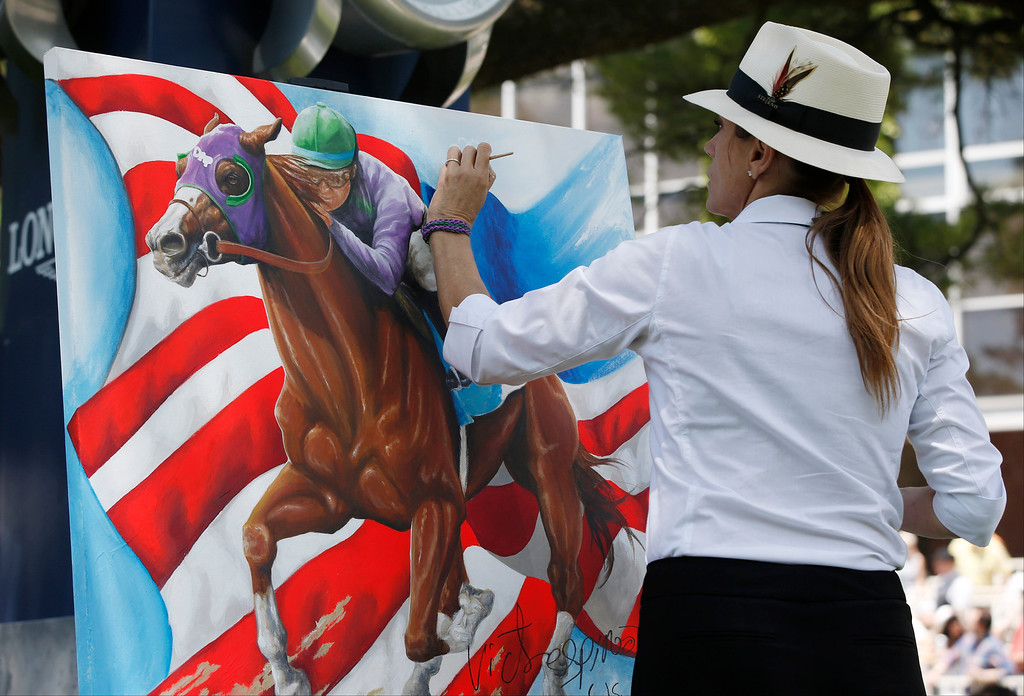 . Artist Susan Sommer-Luarca, of Springfield, Mo., paints an image of Triple Crown hopeful California Chrome outside the grandstand at Belmont Park during the undercard races for the Belmont Stakes horse race, Saturday, June 7, 2014, in Elmont, N.Y. (AP Photo/Kathy Willens)