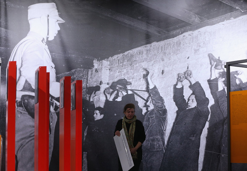 ". A museum worker assembles the final exhibits at the exhibition ""Berlin 1933 - The Path To Dictatorship\"" at the Topography of Terror documentation center and museum under a photograph showing political prisoners guarded over by an SA guard on January 29, 2013 in Berlin, Germany. The exhibition, which opens officially tomorrow, examines the period in 1933 shortly after Adolf Hitler assumed power and the Nazis began murdering and intimidating political opponents as well as persecuting Jews. 2013 marks the 80th anniversary of the Nazi assumption of power.  (Photo by Sean Gallup/Getty Images)"