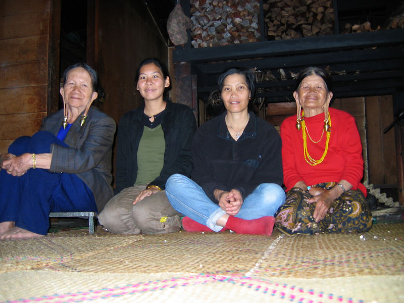 juliet in a longhouse with sumi and a couple of kelabit elders with traditional stretched ears