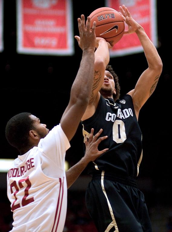 . Colorado guard Askia Booker (0) shoots over Washington State guard Royce Woolridge (22) during the first half of an NCAA college basketball game Saturday, Jan. 19, 2013, in Pullman, Wash. (AP Photo/Dean Hare)