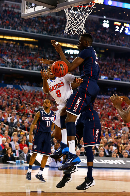 . ARLINGTON, TX - APRIL 05: Kasey Hill #0 of the Florida Gators goes to the basket as Amida Brimah #35 of the Connecticut Huskies defends during the NCAA Men\'s Final Four Semifinal at AT&T Stadium on April 5, 2014 in Arlington, Texas.  (Photo by Tom Pennington/Getty Images)