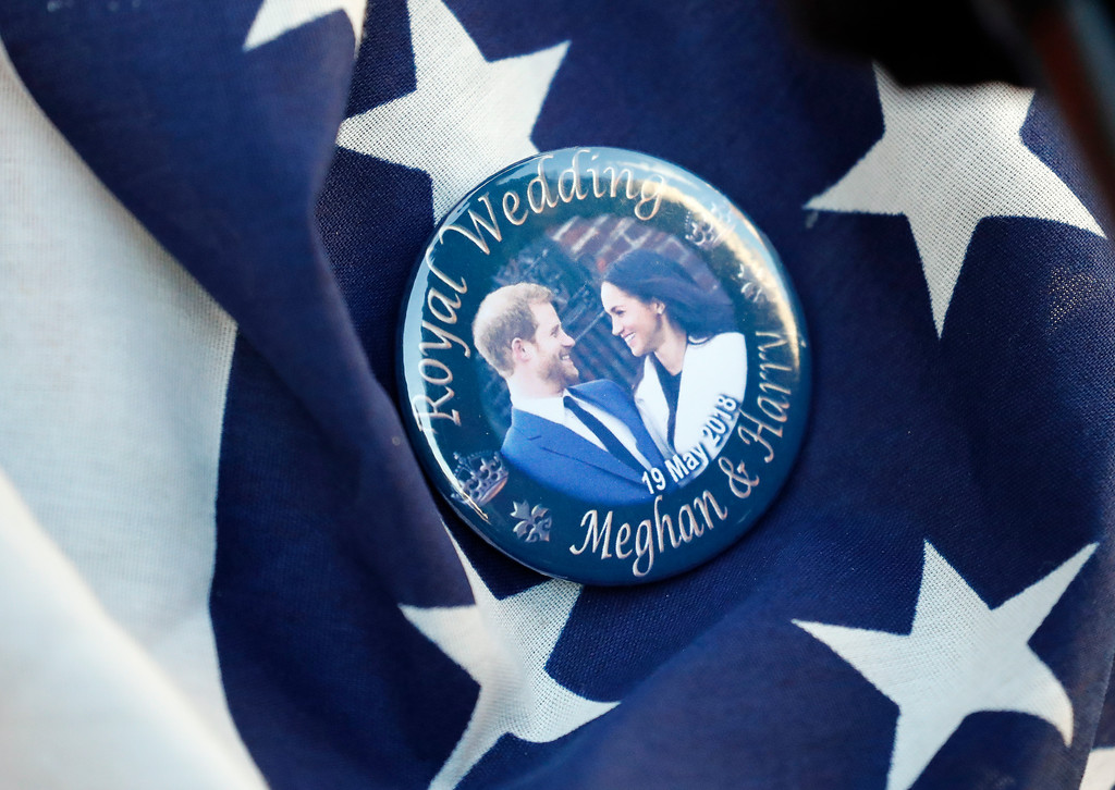 . A badge showing Prince Harry and Meghan Markle is pinned onto a US flag in Windsor, England, Thursday, May 17, 2018. Preparations are being made in the town ahead of the wedding of Britain\'s Prince Harry and Meghan Markle that will take place in Windsor on Saturday May 19. (AP Photo/Frank Augstein)