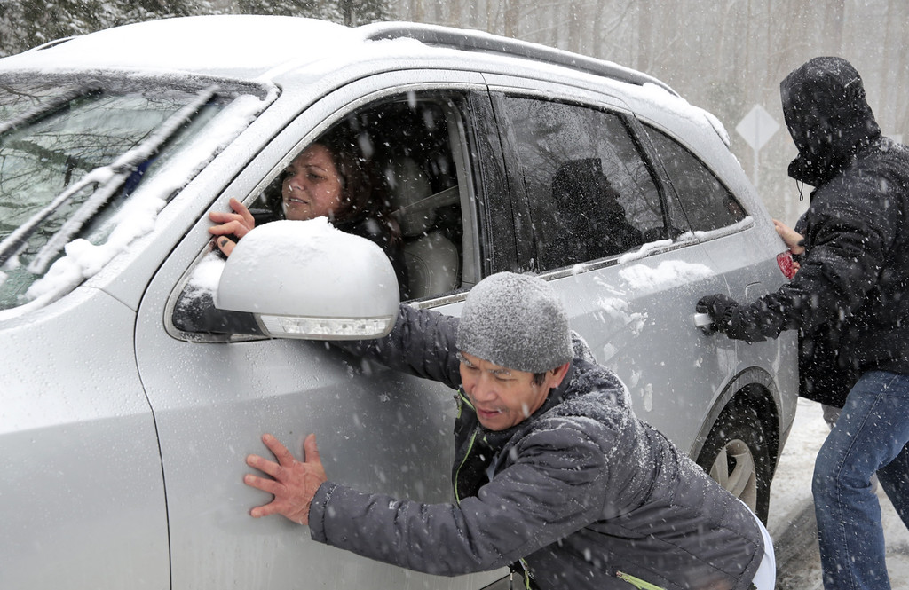 . Melanie Ridlon gets help up a slick hill along Seawell School Rd. in Chapel Hill, NC, during a snow storm on Wednesday, Feb. 12, 2014.  Several cars, including a school bus, were stranded on the hill as snow continued to fall.  (AP Photo/Ted Richardson)