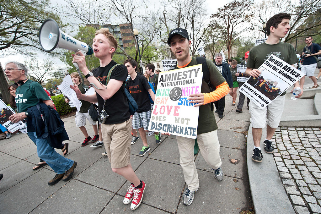 ". Supporters of Amnesty International demonstrate in favor of LGBT (lesbian, gay, bisexual, and transgender) rights at Dupont Circle in Washington on April 12, 2013 as Amnesty International USA holds a series of rallies outside embassies and in public spaces to show solidarity with political prisoners during the annual ""Get on the Bus\"" event. NICHOLAS KAMM/AFP/Getty Images"