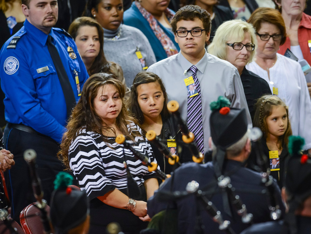 . Ana Hernandez, with children Stephanie and Luis watch look on as the Sheriff bagpipers play at the memorial for their husband and father, Gerardo Hernandez at the Los Angeles Sports Arena Tuesday, November 12, 2013.  A public memorial was held for Officer Hernandez who was killed at LAX when a gunman entered terminal 3 and opened fire with a semi-automatic rifle.  ( Photo by David Crane/Los Angeles Daily News )