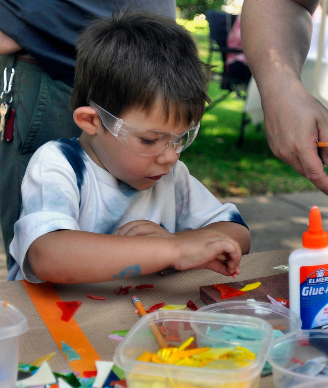. Five year-old Logan Cross makes a Mothers Day gift at the Artist Community of Whittier\'s stained glass mosaic booth.  The 119th anniversary of the founding of Whittier was celebrated during Founders Day at Central Park in Uptown Whittier, Saturday, May 11, 2013.  (Mike Mullen)