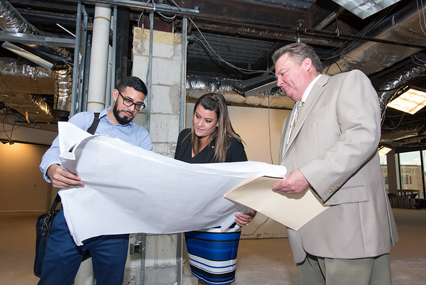 09/05/18 Wesley Bunnell | Staff Architect Arturo Arroyo from Svigals & Partners looks over blueprints with Mayor Erin Stewart and TBI Constructions Ken Johson detailing upcoming renovations to CMHA's newest building located at 233-235 Main St on Wednesday afternoon. The building will undergo renovations in preparation for CMHA's occupancy which was previously planned for 227 Main St.