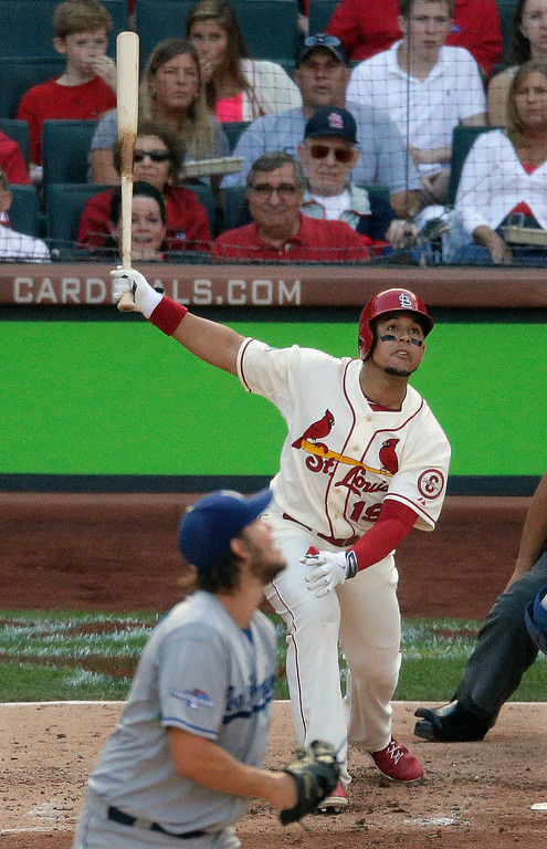 . St. Louis Cardinals\' Jon Jay watches his sacrifice fly in front of Los Angeles Dodgers starting pitcher Clayton Kershaw during the sixth inning of Game 2 of the National League baseball championship series Saturday, Oct. 12, 2013, in St. Louis. (AP Photo/Chris Carlson)