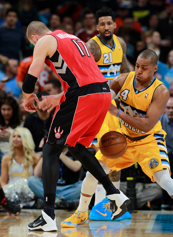 . Toronto Raptors center Jonas Valanciunas, front left, of Lithuania, loses control of the ball as Denver Nuggets guard Randy Foye, front right, defends during the fourth quarter of the Raptors\' 100-90 victory in an NBA basketball game in Denver on Friday, Jan. 31, 2014. Nuggets forward Wilson Chandler is at rear. (AP Photo/David Zalubowski)