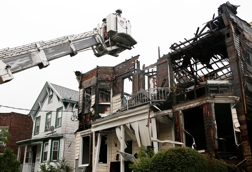 . A firefighter uses a ladder to examine the damaged roof of 203 and 205 Chestnut Avenue in the Staten Island borough of New York, Thursday, June 5, 2014 after fire tore through three adjacent townhouses early Thursday, injuring 34 people. Witnesses and authorities said two young children were tossed out of a window into the arms of neighbors below. (AP Photo/Kathy Willens)