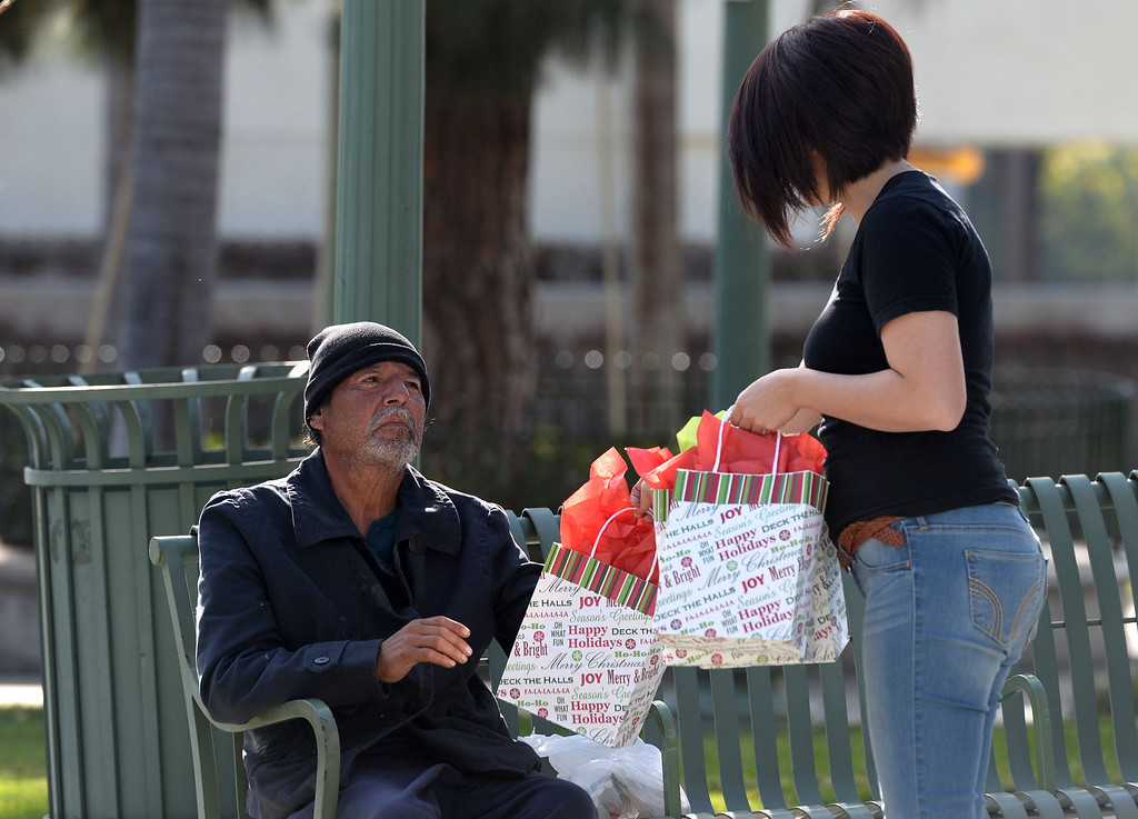 . Jessica Zuniga, right, hands out a gift bag to a homeless man at the Whittier transportation Center in Whittier, Calif., on Saturday, Jan.4, 2014. Zuniga was given a large sum of money by an unidentified man at Target when he thought she had no money.   (Keith Birmingham Pasadena Star-News)