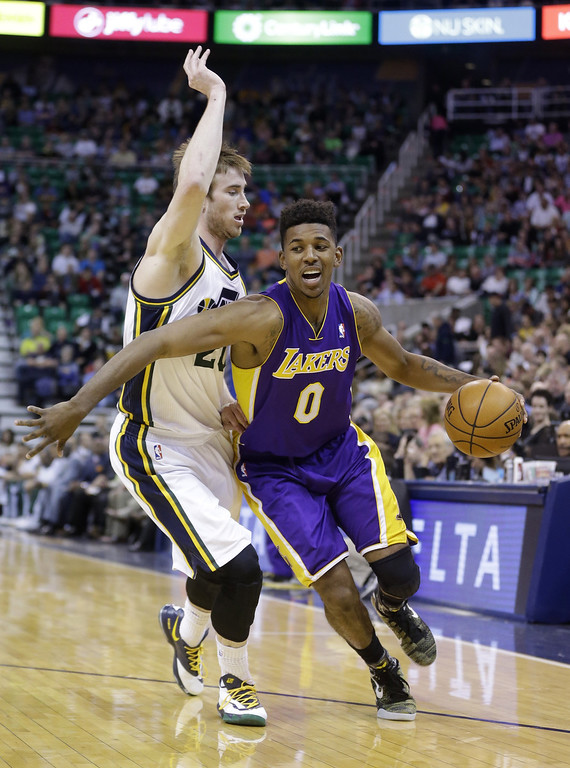. Los Angeles Lakers Nick Young (0) drives around Utah Jazz\'s Gordon Hayward, left, in the first quarter during an NBA basketball game Monday, April 14, 2014, in Salt Lake City, Utah. (AP Photo/Rick Bowmer)