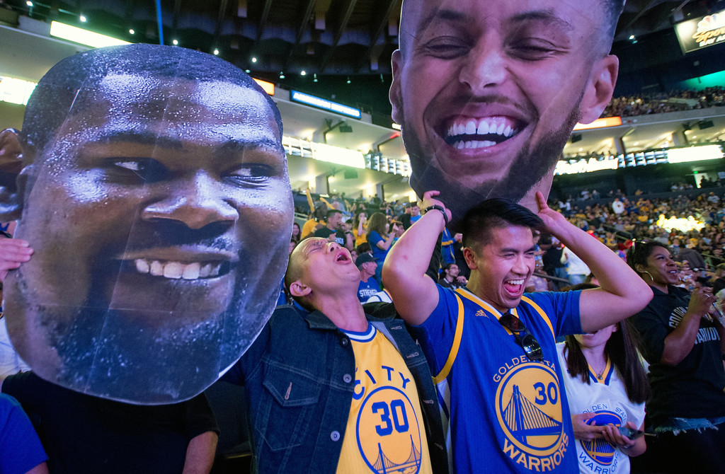 . Fans react while watching television coverage of the Golden State Warriors playing the Cleveland Cavaliers in Game 4 of the NBA Finals, at Oracle Arena in Oakland, Calif., Friday, June 8, 2018. (AP Photo/Josh Edelson)