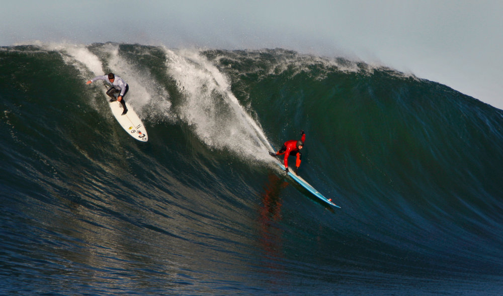 . Dave Wassel, left, and Peter Mel take off on a wave during Round One of the Mavericks Invitational on Sunday, January 20, 2013 at Princeton-by-the-Sea, Calif. Mel was later named the winner of the 2013 Mavericks Invitational. (Karl Mondon/Staff)