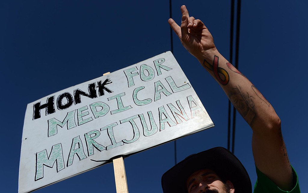 . George Lanzas, 33 of Hesperia and manager of Doc Holliday\'s Collective, in Mentone, joins supporters in protest of the closure of the medical marijuana dispensary Monday August 12, 2013.  (Photo by Rick Sforza/Redlands Daily Facts)