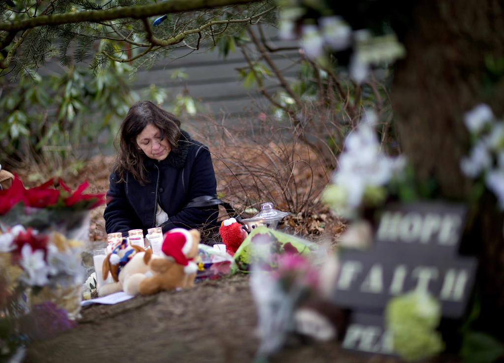 . Dilma Steiner, of Newtown, Conn., visits a sidewalk memorial for the Sandy Hook Elementary School shooting victims, Sunday, Dec. 16, 2012, in Newtown, Conn. A gunman walked into Sandy Hook Elementary School in Newtown Friday and opened fire, killing 26 people, including 20 children. (AP Photo/David Goldman)