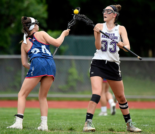 5/31/2018 Mike Orazzi | Staff St. Paul Catholic High School's Cameron Baston (24) and North Branford High School's Jessie Kilburn (33) during the girls Class S Quarterfinals lacrosse at North Branford High School Thursday evening.