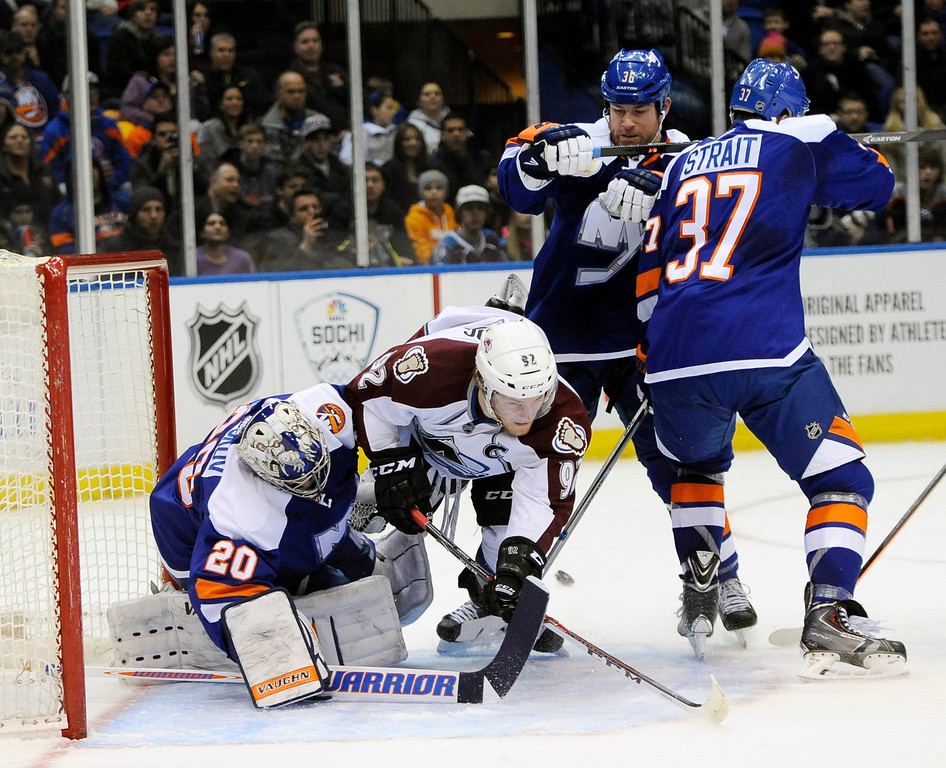 . Colorado Avalanche\'s Gabriel Landeskog (92) crashes into New York Islanders goalie Evgeni Nabokov (20) leaving the puck behind for Avalanche Nathan MacKinnon to score as Islanders\' Eric Boulton (36) and Brian Strait (37) try to defend in the first period of an NHL hockey game on Saturday, Feb. 8, 2014, in Uniondale, N.Y. (AP Photo/Kathy Kmonicek)