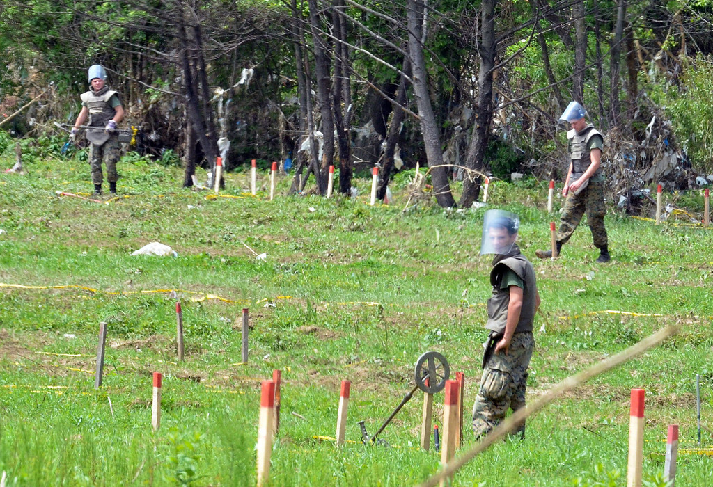 . Bosnian mine clearance experts search a field after flood waters receded from the village of Cekrekcije, near Sarajevo, on May 20, 2014. The river Bosna flooded entire agricultural fields and several urban areas along its flow, during the weekend\'s rainfall, which also caused landslides. The number of remaining land mines and entire land mine fields in Bosnia is not precise but authorities fear that they might have shifted during the flooding and due to landslides countrywide. AFP PHOTO / ELVIS BARUKCIC/AFP/Getty Images