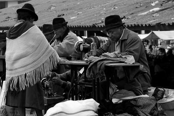 Men altering clothes in Saquisili market, Ecuador