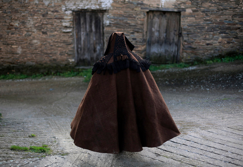 Description of . A penitent walks along a street following a procession of