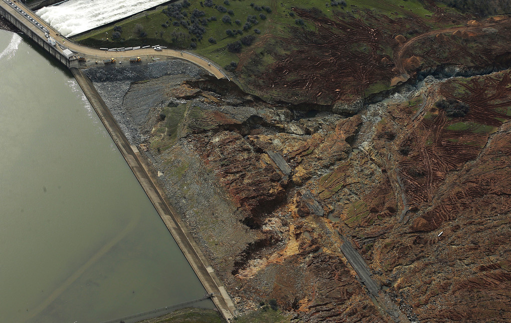 . This photo shows erosion caused when overflow water cascaded down the emergency spillway of Oroville Dam, Monday, Feb. 13, 2017, in Oroville, Calif. Water levels dropped Monday at the nation\'s tallest dam, easing slightly the fears of a catastrophic spillway collapse that prompted authorities to order people to leave their homes downstream. At upper left, water flows down the dams main spillway. (AP Photo/Rich Pedroncelli)