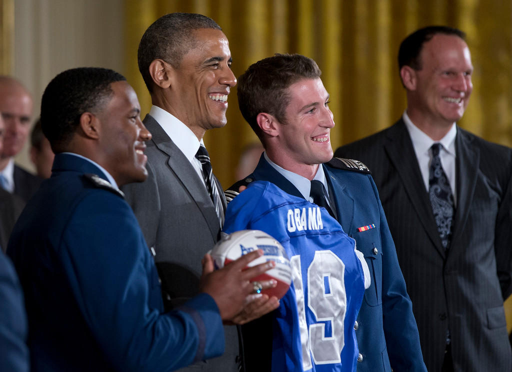 . President Barack Obama poses with a football and jersey given to him by U.S. Air Force Academy football defensive back Christian Spears, left, and quarterback Kale Pearson, third from left, during an event in the East Room of the White House in Washington, Thursday, May 7, 2015, where he honored them with the Commander-in-Chief Trophy. At right is head coach Troy Calhoun. (AP Photo/Carolyn Kaster)
