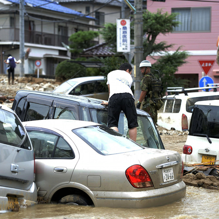 . A man tries to walk through a flooded area by crawling over cars swept and stuck in the muddy water after a massive landslide swept through residential areas in Hiroshima, western Japan, Wednesday, Aug. 20, 2014.  (AP Photo/Kyodo News)