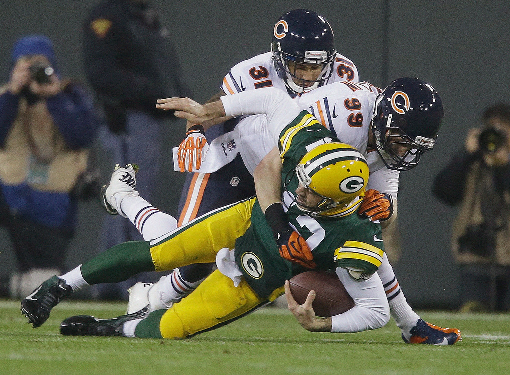 . Green Bay Packers quarterback Aaron Rodgers is sacked by Chicago Bears\' Shea McClellin (99) and Isaiah Frey (31) during the first half of an NFL football game Monday, Nov. 4, 2013, in Green Bay, Wis. Rodgers left the game after the play. (AP Photo/Jeffrey Phelps)