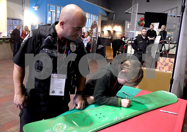 12/7/2017 Mike Orazzi | Staff Southington police officer Kevin Naranjo as Jared Beers signs a snowboard during a meet and greet held at Crystal Bees in Southington before shopping for Shop with a Cop, a one on one shopping experience pairing underprivileged children with law enforcement.