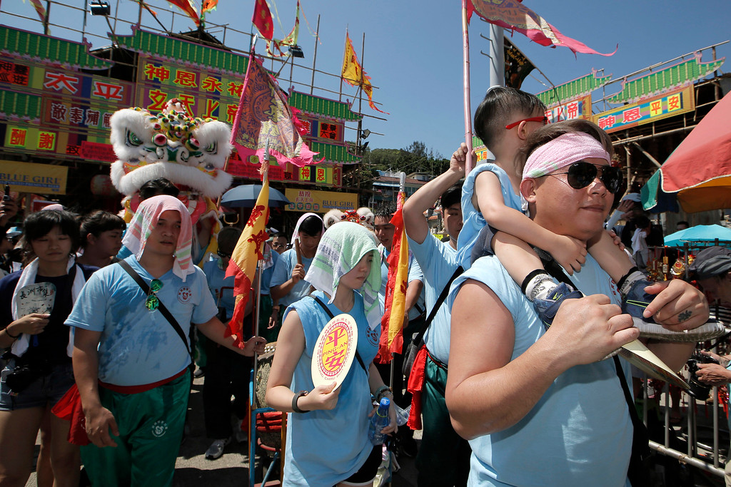 . Villagers brave the heat during a parade on the outlying Cheung Chau island in Hong Kong to celebrate the Bun Festival Tuesday, May 22, 2018. Bun Festival, the Taoist God of the Sea, is worshipped and evil spirits are scared away by loud gongs and drums during the procession. The celebration includes bun scrambling, parades, opera performances, and children dressed in colorful costumes. (AP Photo/Kin Cheung)