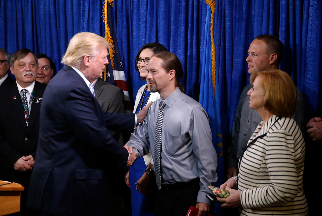 . Republican presidential candidate Donald Trump, right, shakes hands with John Trandem, one of the 22 delegates from North Dakota to the Republican National Convention, who are the core of delegates that elevated Trump over the 1237 needed for the GOP\'s presidential nomination, Thursday, May 26, 2016, in Bismarck, N.D. (AP Photo/Charles Rex Arbogast)