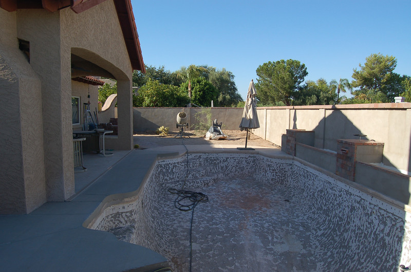 The pool has been chipped out in preparation for pebble tech. The planters and water feature have been installed on the far side of the pool.