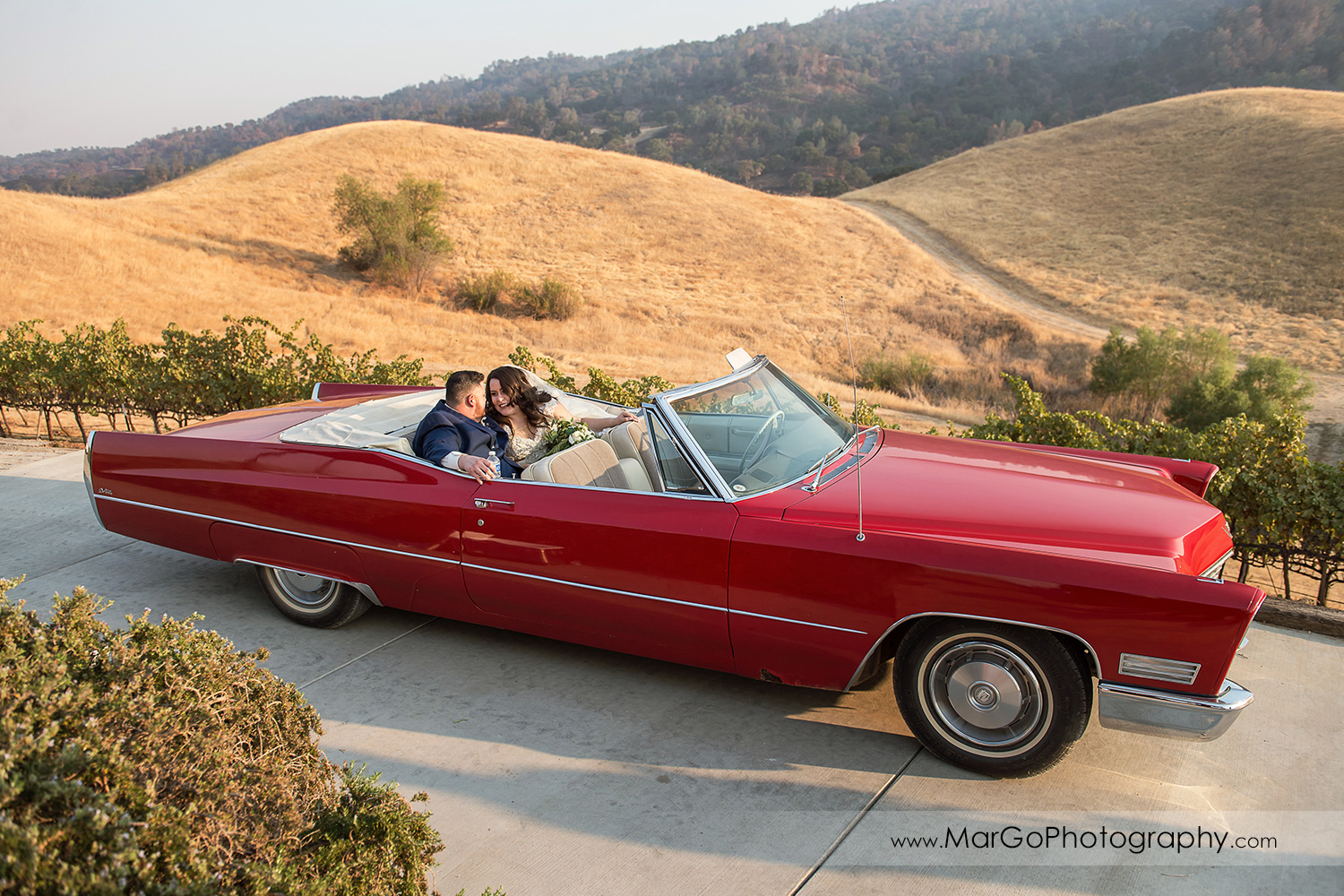 bride and groom sitting in the red convertible at Taber Ranch Vineyards
