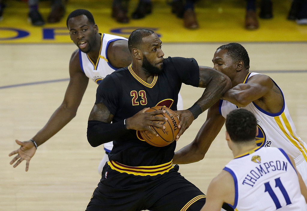 . Cleveland Cavaliers forward LeBron James (23) shoots between Golden State Warriors forward Draymond Green, top, guard Klay Thompson (11) and forward Kevin Durant during the first half of Game 2 of basketball\'s NBA Finals in Oakland, Calif., Sunday, June 4, 2017. (AP Photo/Ben Margot)