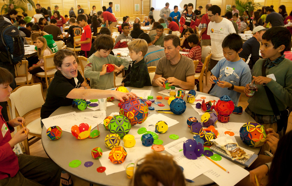 . Volunteers and students work on math problems at Stanford University in Stanford Saturday May 11, 2013.  About 350 students in grades 6�12 tested their brainpower and enjoyed a hands-on learning experience covering a wide variety of math topics at the Julia Robinson Mathematics Festival at Stanford. Students circulated among activity tables where teachers, professors, graduate students, and others engaged the youths as they tested their math skills on puzzles, games, and problems.  (Patrick Tehan/Bay Area News Group)
